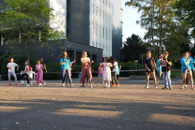 Eine Kinder- und Jugendgruppe studiert einen Flashmob ein.