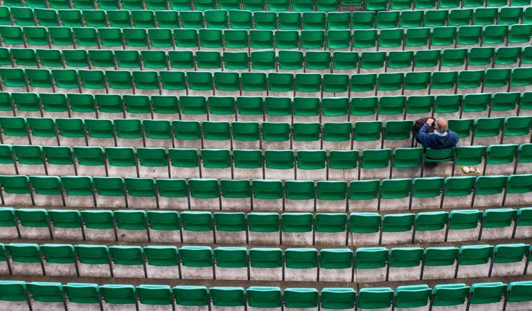 Ein Mann sitzt ganz alleine auf einer Tribüne. Alle anderen Sitzplätze sind leer.