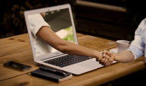 Der Arm einer Person kommt aus dem Bildschirm eines Laptops heraus und schüttelt die Hand einer anderen Person, die vor ihrem Laptop an einem Tisch sitzt. Online Verbundenheit kann die Offline Verbundenheit stärken.