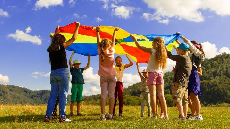 Eine Gruppe Kinder spielt zusammen mit ihrer Jugendleiterin.