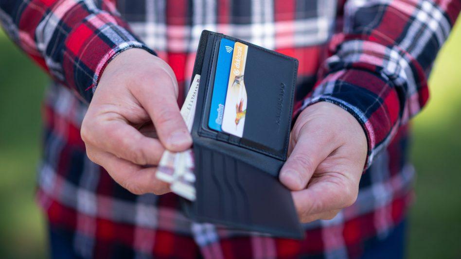 Ein Mann hat sein Portemonnaie mit Bargeld und Karten in der Hand und ist gerade dabei, einen Geldschein herauszuziehen.