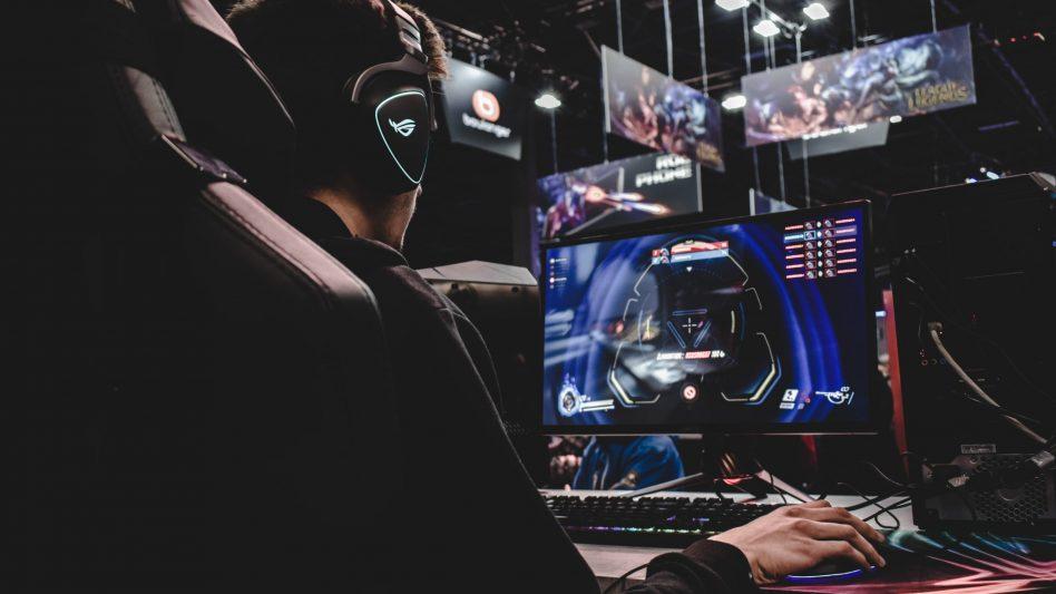 Ein eSports Spieler sitzt an seinem Computer und spielt konzentriert.
